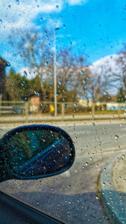 Water drops on a car windshield in sunny day. View on the road through the window glass of the car covered by rain drops