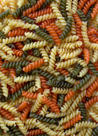 Tricolor, dry and raw pasta, food for background