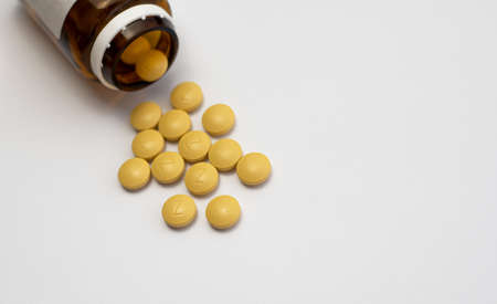 Iron is a very valuable and one of the most important minerals in our body. Front view of a brown bottle with several yellow iron tablets spilling onto on a white background