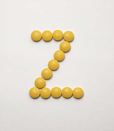 Iron in yellow tablets arranged in the letter Z on a white background