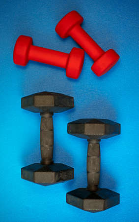 Equipment for exercising the muscles of the hands and arms. A pair of weights on a blue background