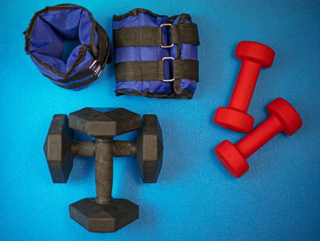 Equipment for exercising the muscles of the arms and legs. Weights and sandbags on a blue background