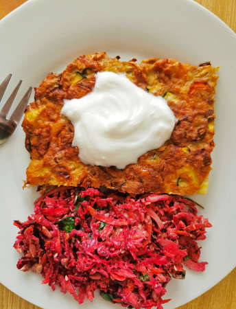 A healthy and tasty vegetable casserole served with natural yogurt and a salad of red beetroot, carrot and green parsley. Delicious breakfast, lunch or dinner
