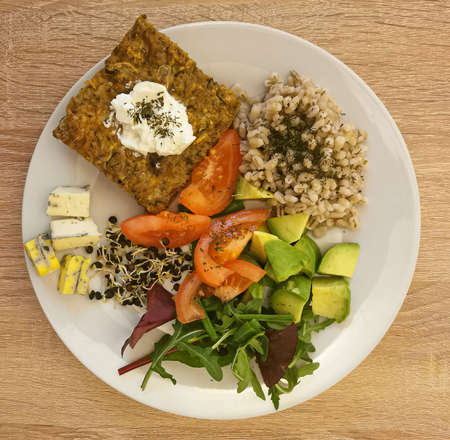 Cooked pearl barley, a piece of vegetable casserole with cream or natural yoghurt. Pieces of cheese with mold, tomato, avocado, arugula leaves, beetroot leaves, black lentil sprouts Banque d'images