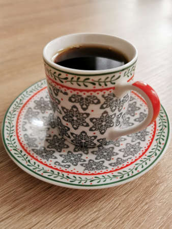 Image of a cup of black coffee on a wooden table