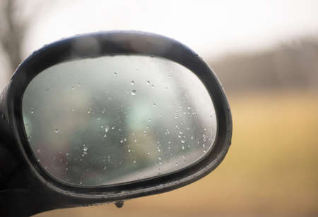 Car side view mirror with rain drops