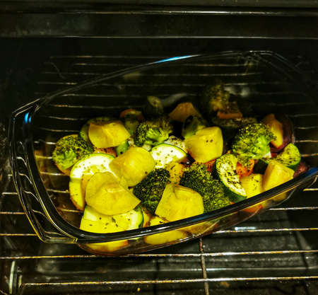 Tasty and colored vegetable mix with spices and olive oil. Baked vegetables in the oven. Potatoes, broccoli, beets, zucchini, carrots, apples in a glass bowl