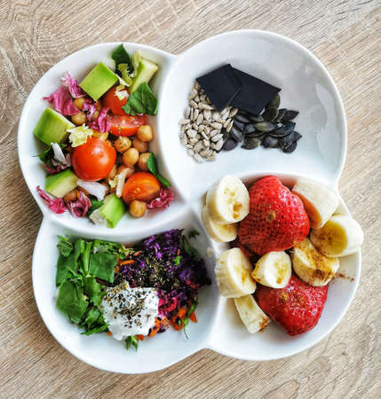 A healthy, tasty and colorful breakfast: chickpeas, tomato, avocado, carrot, spinach and parsley leaves, red cabbage. Pieces of black chocolate, pumpkin and sunflower seeds, banana and strawberries
