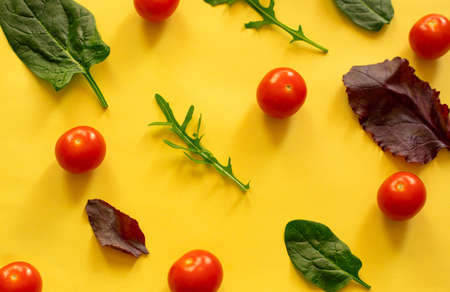 Cherry tomatoes, beet leaves, spinach leaves and arugula leaves on a yellow background