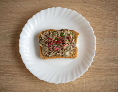 Healthy, tasty sandwich with dark bread, fish paste, avocado and beetroot alfalfa sprouts on a white plate