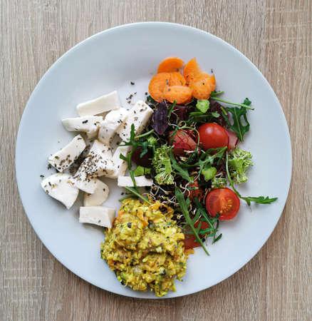 Healthy food - organic tomato and vegetable salad, broccoli, carrot, arugula leaves, mozzarella cheese