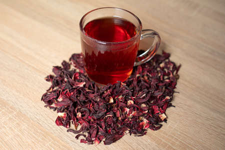 A cup of red tea with hibiscus flowers on a wooden table Stock Photo
