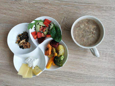 A healthy and nutritious breakfast. Porridge with chia seeds, vegetables, nuts and cheese Zdjęcie Seryjne