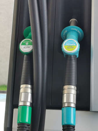 Pistols of gasoline fueling cars at the station. Warsaw, Poland, April 18, 2021