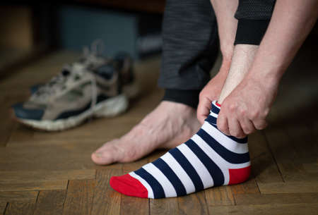 The man is putting colorful striped socks and shoes shown on background