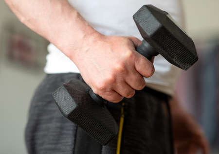 Training with dumbbells at home. The man is exercising at home. Closeup of a male hand with a dumbbell 5 kg Zdjęcie Seryjne