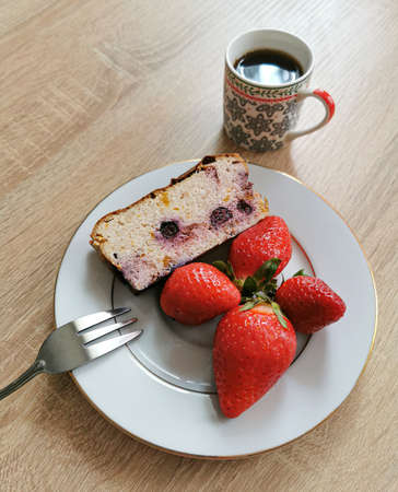 A piece of homemade cheesecake with blueberries, strawberries on a white plate and coffee