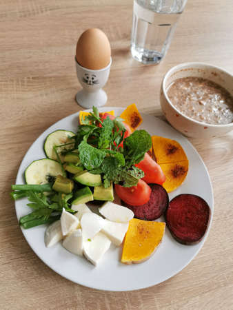 A healthy breakfast rich in protein, fats and carbohydrates. Oatmeal with nuts, soft-boiled egg, mocarella cheese, colorful vegetables, green leaves of mint, parsley and onion Zdjęcie Seryjne