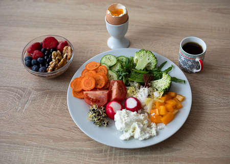 A healthy and tasty breakfast. Soft boiled egg, cottage cheese, colorful vegetables, berries, nuts and coffee