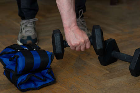 Equipment for exercising the muscles of the arms and legs. Weights and sandbags on the wooden floor. The man takes a dumbbell and picks it up with one hand