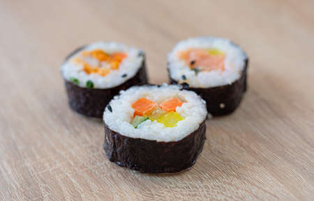 Three rolls of sushi on a wooden background