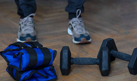 Equipment for exercising the muscles of the arms and legs. Weights and sandbags on the wooden floor