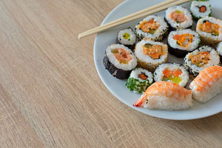 Closeup on sushi set of maki with chopsticks on a white plate