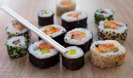 Sushi set of maki with chopsticks on wooden background for menu Zdjęcie Seryjne