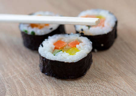 Three sushi rolls with chopsticks on a wooden background