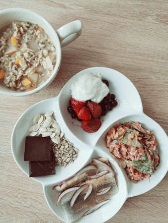 A healthy breakfast for your brain. Oatmeal (porridge) with chia seeds and apple and pumpkin. Herring, vegetable salad, blueberries, sunflower seeds, and two pieces of dark chocolate