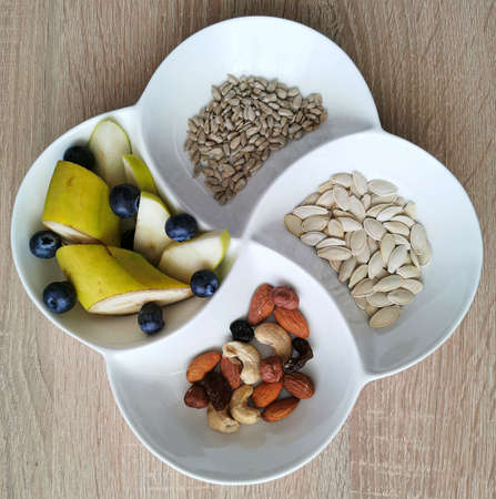 A healthy snack. Nuts, sunflower and pumpkin seeds. Banana pieces, apples and blueberries Zdjęcie Seryjne