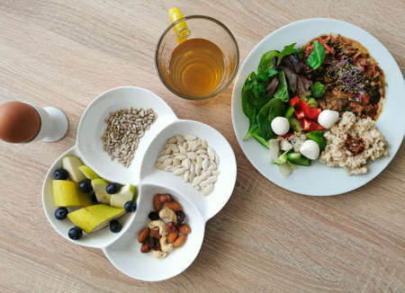 A healthy delicious breakfast with protein, fat and carbohydrates. Soft boiled egg. Oatmeal with cinnamon, mocarella cheese, boiled and raw vegetables. Nuts, sunflower and pumpkin seeds. Fruits, tea Zdjęcie Seryjne