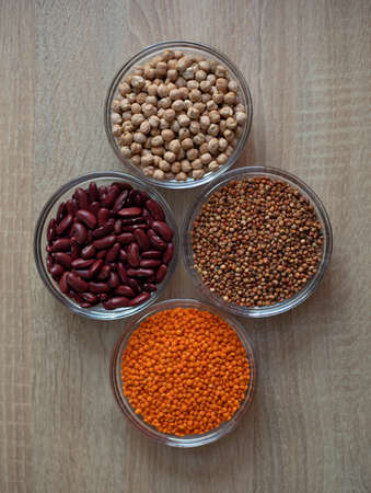 Bowls of cereal grains: chickpeas, red lentils, red bean, sorghum grain