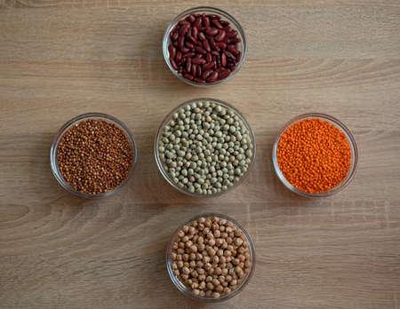 Bowls of cereal grains: chickpeas, red lentils, red bean, green peas, sorghum grain Zdjęcie Seryjne