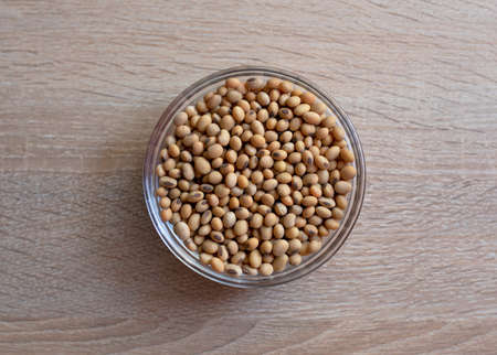 Bowl of raw grain soybeans on a wooden table