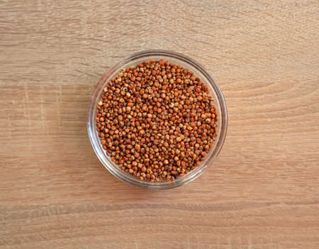 Bowl of raw sorghum grain on a wooden table