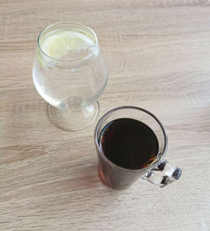 Coffee and water in a glass with lemon on a wooden table Zdjęcie Seryjne