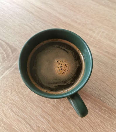 Top view of green cup of black coffee with some bubbles on a wooden table Zdjęcie Seryjne