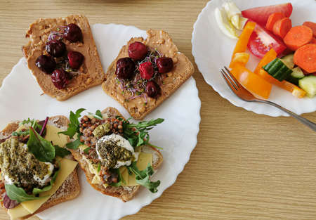 Four healthy sandwiches with dark wholemeal bread. Two savory and two sweet sandwiches. One serving of fresh vegetables