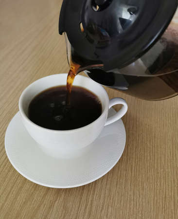 Break on coffee drink. Mug of hot filtered coffee from a glass pot Zdjęcie Seryjne