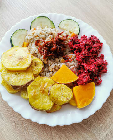 Pearl barley with soybeans, carrots, dried tomatoes. Baked potatoes, pumpkin and zucchini. Salad with beetroot, carrot, arugula leaves, spinach and garlic