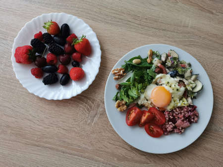 A healthy and tasty summer breakfast. Soft boiled egg, buckwheat groats, colorful vegetables, nuts and berries Zdjęcie Seryjne
