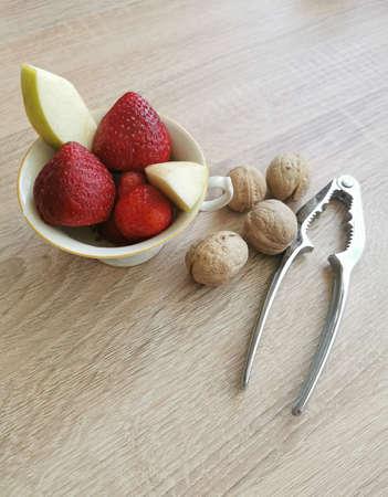 Fresh strawberries, apple pieces, walnuts and a nutcracker Zdjęcie Seryjne