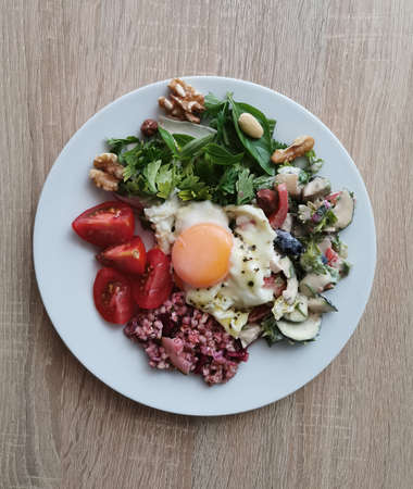 A healthy and tasty summer breakfast. Soft boiled egg, buckwheat groats, colorful vegetables and nuts Zdjęcie Seryjne