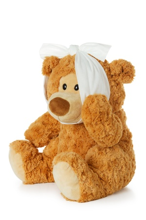 Teddybear with toothache holding his jaw and isolated on a white background photo
