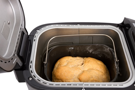 Fresh homemade bread in the electric bread maker on a white background photo