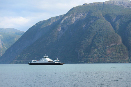 fjord: A ferry is floating across fjord.