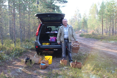 leningradskaya: Man with a basket of cepes mushrooms in the forest and a car on background. Stock Photo