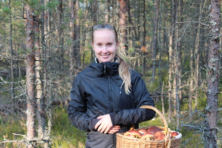 gatherer: Young woman with a basket of mushrooms in the forest