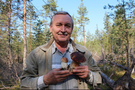 leningradskaya: Man with two cepes mushrooms in the forest.